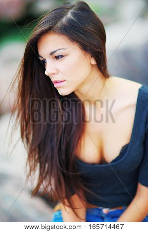 Portrait of young beautiful long-haired brunette woman in a black shirt with a deep neckline on blurred background close up