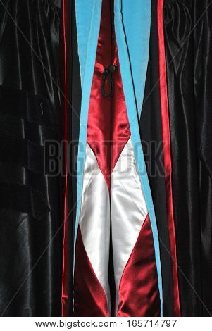 Graduation gown displayed indoors at school ceremony.