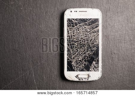 Broken smart phone over a slate stone
