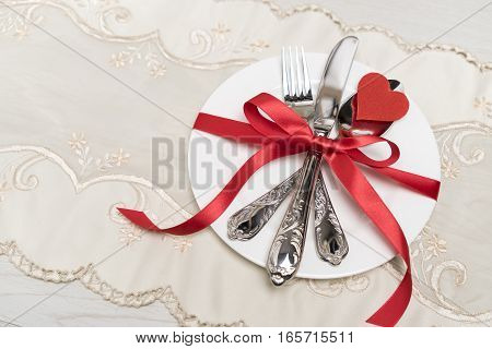 table setting for Valentine's Day. plate, fork, knife and red hearts