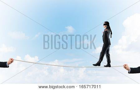 Businessman with blindfolder on eyes walking on rope over sky background