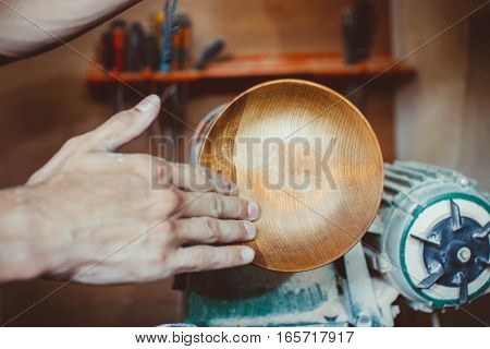 Wood turners using sandpaper polished wood on a lathe