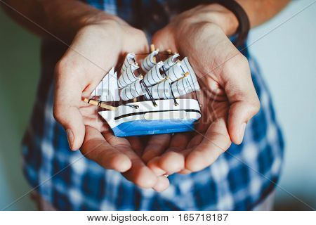 toy ship in the hands in the room on a white background