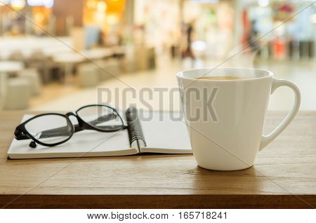 Cup Of Coffee, Eyeglass And Book On Wooden Table In Coffee Shop.