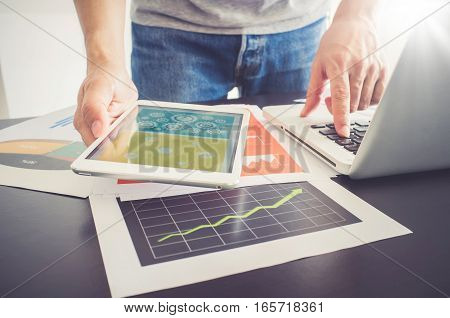 Businessman Working With Digital Tablet And Laptop With Financial Document.