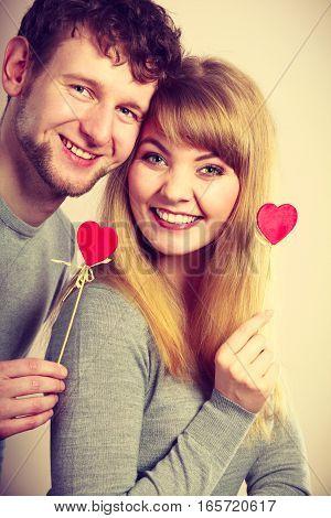 Youthful Couple Holding Hearts.
