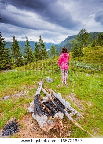 Tourism vacation and travel. Tourist woman in camping site enjoying mountains landscape at summer in Norway Scandinavia.