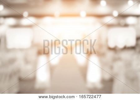 Blur image of dining table in hall for wedding background. Dinner in luxury hotel with people gray tone.