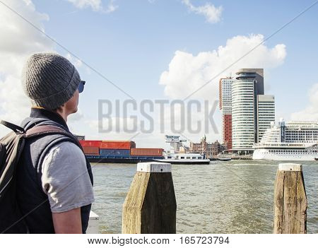 Young modern guy in hat and sunglasses, tourist with backpack looking on Rotterdam city harbour, future architecture concept, industrial lifestyle people close up