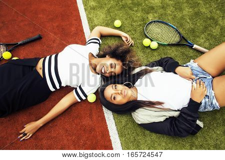 young pretty girlfriends hanging on tennis court, fashion stylish dressed swag, best friends happy smiling together lifestyle close up