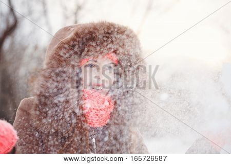 Lovely teen girl in pink knitted gloves hat and scarf fur hooded jacket winter walks in the park. She throws snow up. Outdoor Activities. Youth fashion. Close-up portrait
