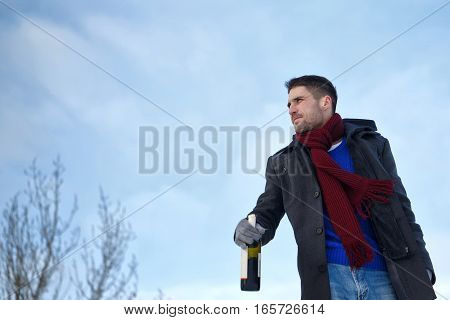 Man walking with a bottle of wine. He is dressed in winter coat scarf and gloves. Shooting from a low angle. Sad face.