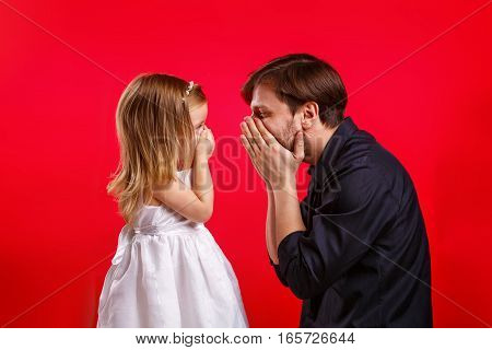 Father and daughter hid his mouth. Emotional games with your child. Family fun. The joy of communication. Nothing to say.