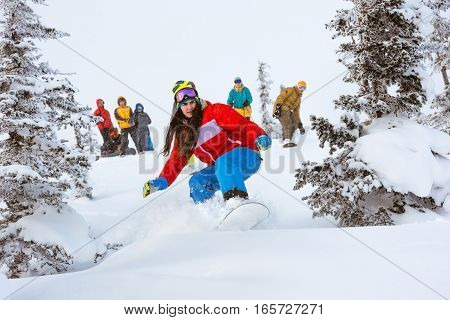 Off-piste snowboarding. Girl freeriding in forest with group of friends