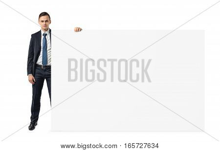Businessman on white background holding a shoulder-height blank display board. Business and finance. Advertizing and promotion. Presentations.