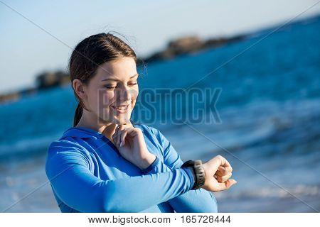 Young girl on beach checking heart rate after run