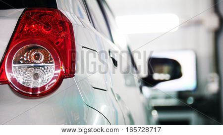Auto service - red backlights of white car, transportation concept, close up