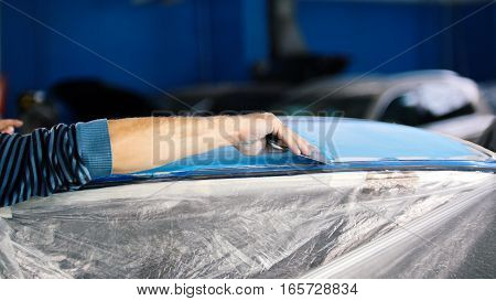 Automobile service - manual labor - polishes car, extremely close up, wide angle