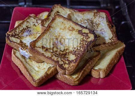 Freshly cooked French Toast Served on a Red Plate.