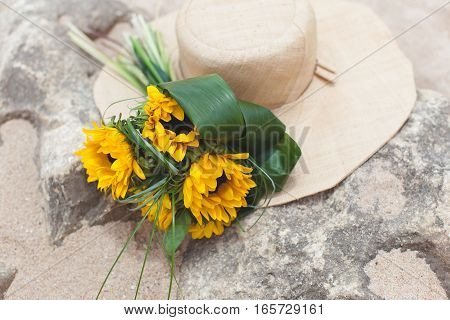 Bouquet of sunflowers and hat on the stone