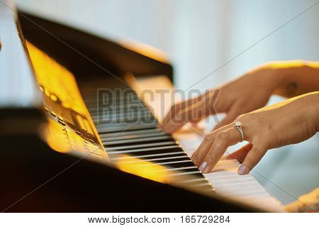 Close-up image of woman with big ring playing the piano