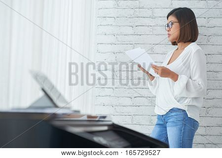 Pensive Asian music composer with music notes