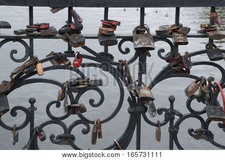 Close up of black metal fence with padlocks of various sizes, shapes and colors attached by couples to celebrate their love and marriage. The Iset  River in Yekaterinburg Russia is seen on the background.