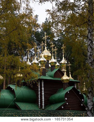 One of seven chapels, the Royal Temple, in the monastery built on the site of the Romanov family's burial. Golden onion domes with crosses top the log Russian Orthodox Church. Surrounded by trees with fall leaves. Located near Yekaterinburg Russia