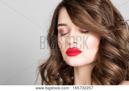 Studio portrait of a beautiful young woman. Fashion Makeup Model with perfect makeup red lips and smooth clean skin