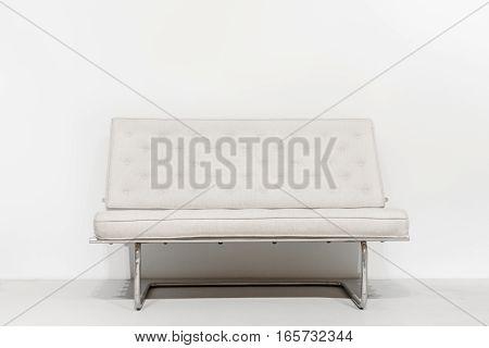 White sofa near white wall in interior. Minimalism modern design.
