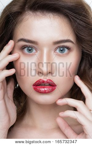 Studio portrait of a beautiful young woman. Fashion Makeup Model with perfect makeup red lips and smooth clean skin.