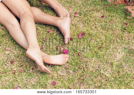 Feet of young romantic couples lying on grass