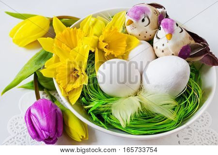 Traditional Czech easter decoration - white eggs with daffodils and tulips with birds in the green grass nest. Spring easter holiday arrangement.