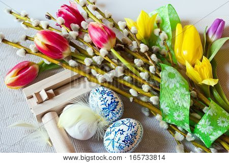 Traditional Czech easter decoration - regional wooden ratchet instrument with painted blue eggs with pussycats and tulips flower. Spring easter holiday arrangement.
