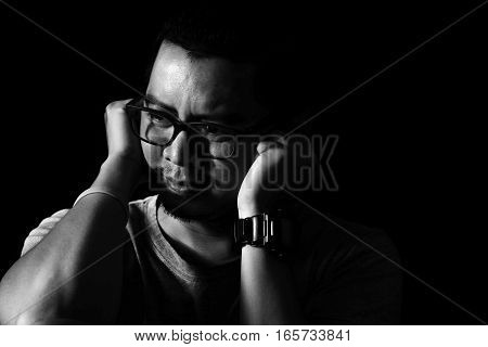 Asian man in the darkness covers his ears in the mood to hear about any depression