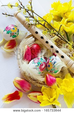 Traditional Czech easter decoration - wooden flute music instrument with painted eggs with daffodils and tulips flower in the nest with white feathers. Spring easter holiday arrangement.