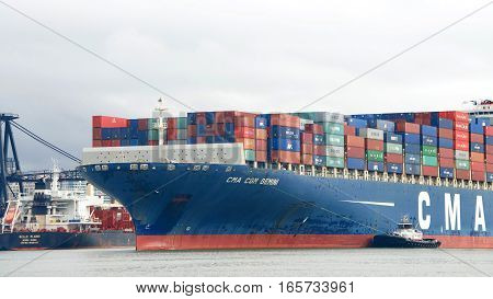 Oakland CA - January 12 2017: Tugboat REVOLUTION off the port side of cargo ship CMA CGM GEMINI assisting the vessel to maneuver into the Port of Oakland.