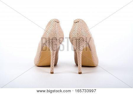 beige elegant ladies' high-heeled shoes on a white background