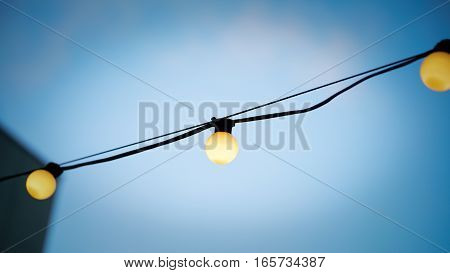Light Bulbs hanging on a wire with blue sky at the background. selective focused