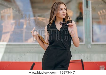 young beautiful brunette enjoys gadgets, photographs, and lunch