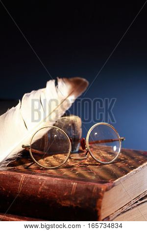 Vintage still life. Quill pen and spectacles on old book