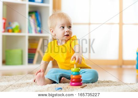 Portrait of cute child boy assembling colorful pyramid on floor at living room