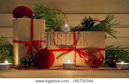 Gifts and sprigs of pine with cones, candles on wooden background