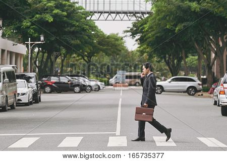 Vietnamese businessman talking on the phone when crossing road