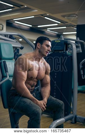 Young bodybuilder looking at the muscles after a workout. Handsome guy sitting on the simulator. Bodybuilder tired after a workout. The man sitting in the gym. A guy with a naked torso. Sexy guy.