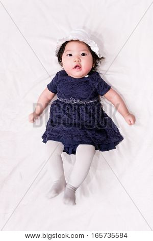 baby girl with cute blue navy dress and white background