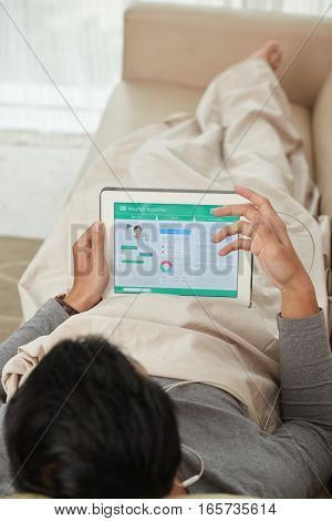 Man lying on sofa and checking his health status in application