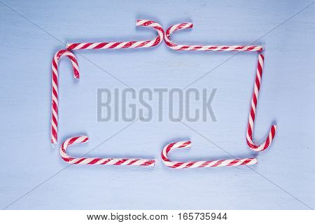 Frame  Of Candy Canes On A Wooden Background. Christmas Sweets And Decorations