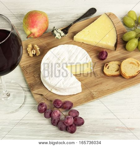 A square photo of a tasting with a glass of red wine, different types of cheese, bread, pear, grapes, on a wooden board with copy space