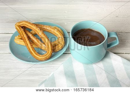 Photo of churros, traditional Spanish, especially Madrid, dessert, in particular for Sunday breakfast. In form of horseshoes, with cup of hot chocolate, on wooden texture with copyspace